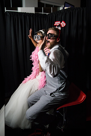 wedding couple taking pictures at the manor at coffee creek photo booth