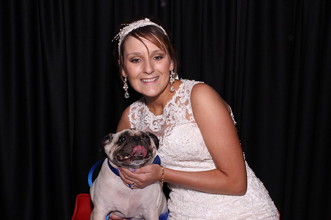 wedding bride with her dog taking pictures at the manor at coffee creek photo booth