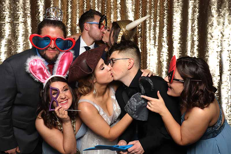 open air photo booth set up ready for wedding, with scrapbook, props, signs, printer, camera and lighting at the 11 oaks ranch venue in luther, oklahoma
