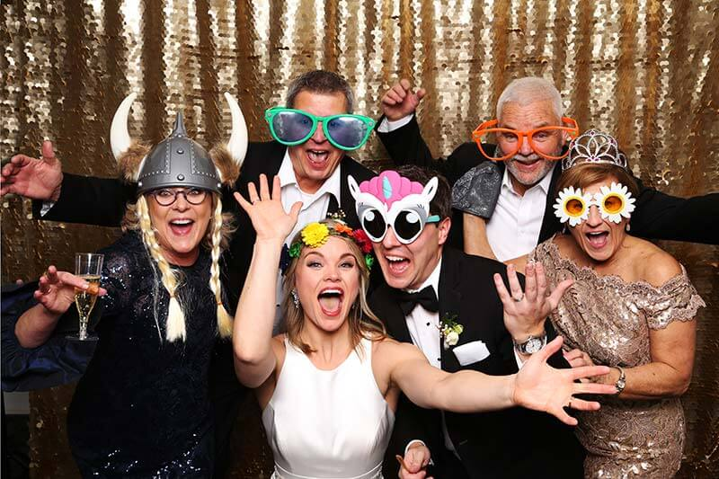 photo booth attendant laughing with guests as they have their pictures snapped in our snap me crazy photobooth in edmond, oklahoma.